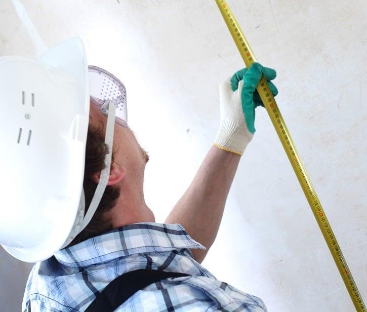 installation contractor measuring wall