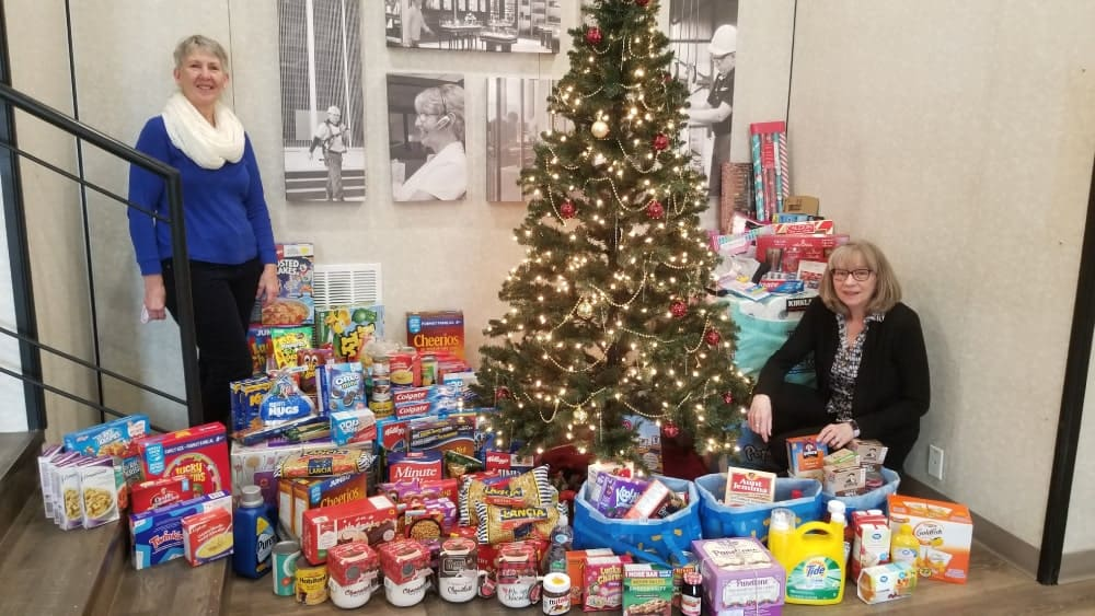 Two Dynamic Employees Stand Beside a Christmas Tree and Donated Food